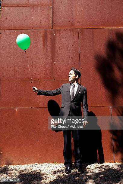Businessman with green balloon