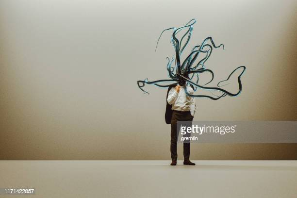 businessman with growing tentacles - tentacle stock pictures, royalty-free photos & images