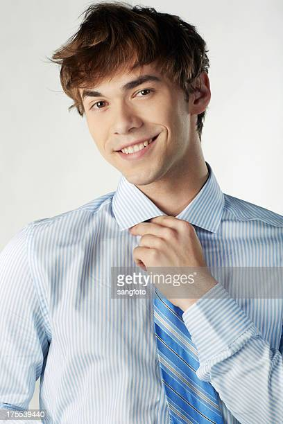 Businessman with hand adjusting tie and smiling