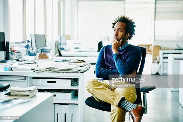 businessman with hand on chin seated in office - decisão - fotografias e filmes do acervo