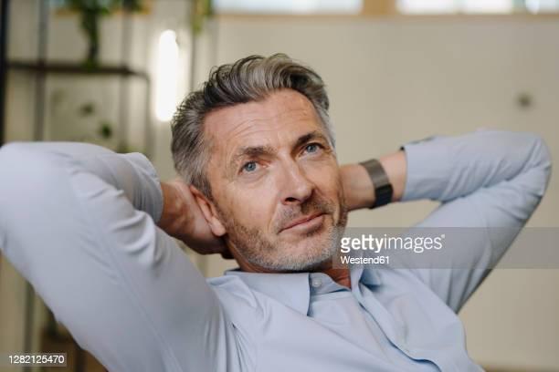 businessman with hands behind head relaxing while sitting at office - hände hinter dem kopf stock-fotos und bilder