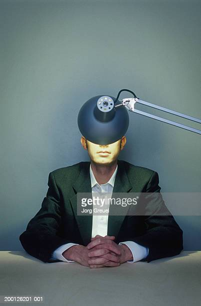 Businessman with hands clasped, illuminated lamp obscuring face