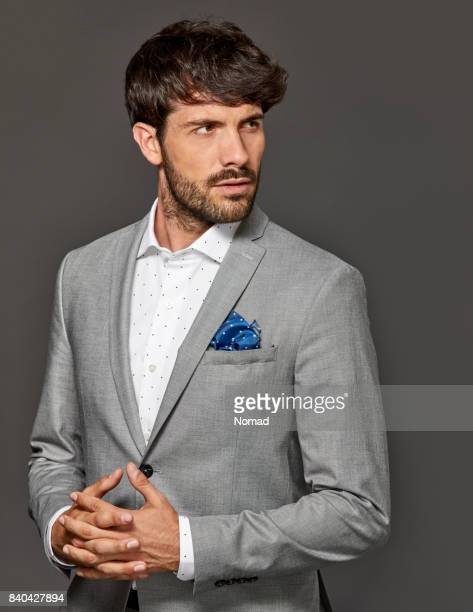 Businessman with hands clasped looking away