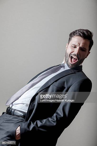 Businessman with hands in pockets mouth open