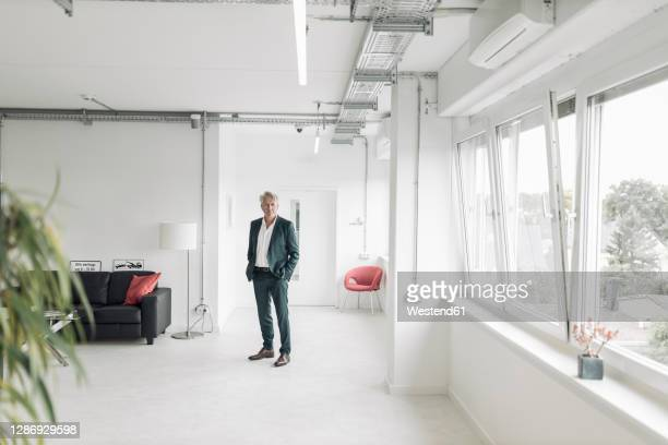 businessman with hands in pockets standing at new office - focus on background stock pictures, royalty-free photos & images