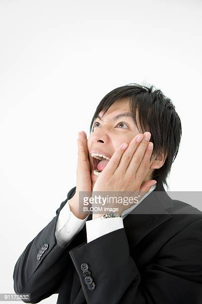 Businessman with hands on cheeks with surprised expression