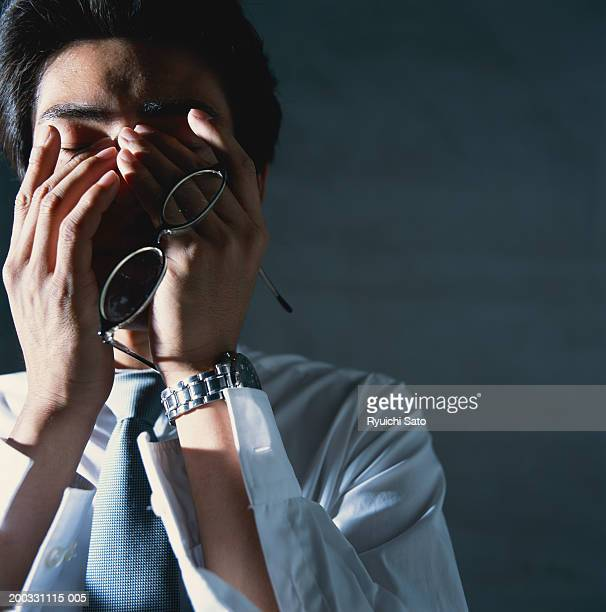 Businessman with hands on face, eyes closed