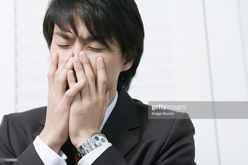 Businessman with hands over mouth : Stock Photo