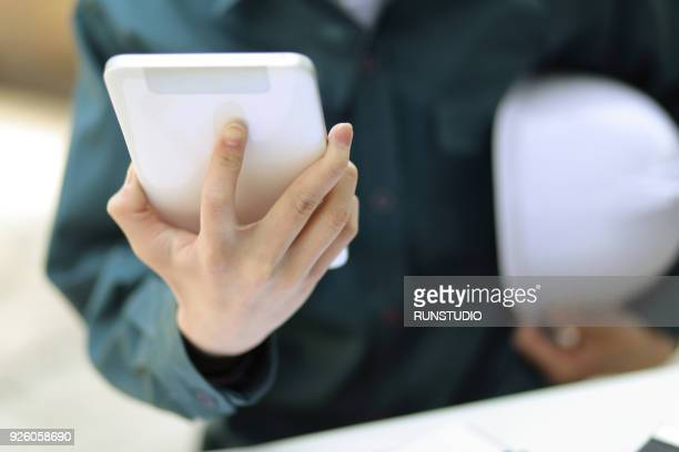 Businessman with hardhat using digital tablet on table