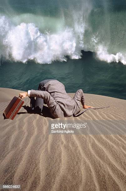Businessman with head buried in sand