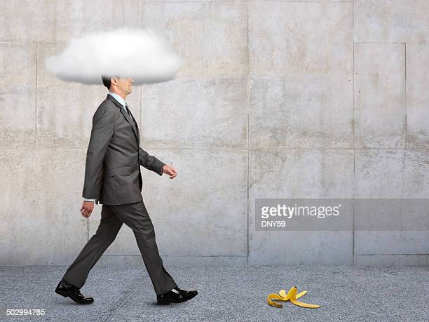 businessman with head in clouds with banana peel in path - blindfolded stock photos and pictures