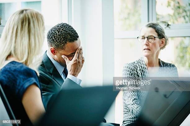 Businessman with head in hand during meeting