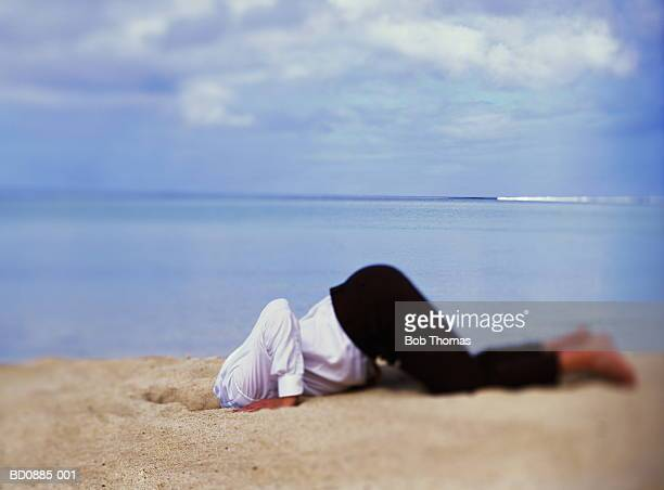 Businessman with head in sand, sea in background