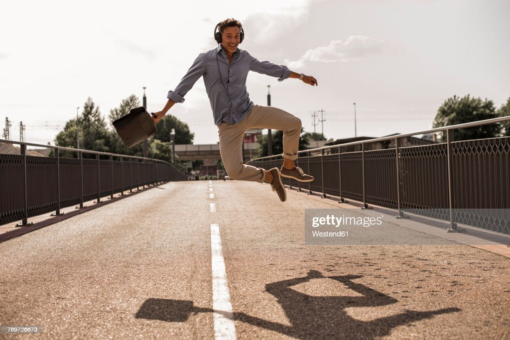 Businessman with headphones and briefcase jumping for joy on a road : Stock-Foto