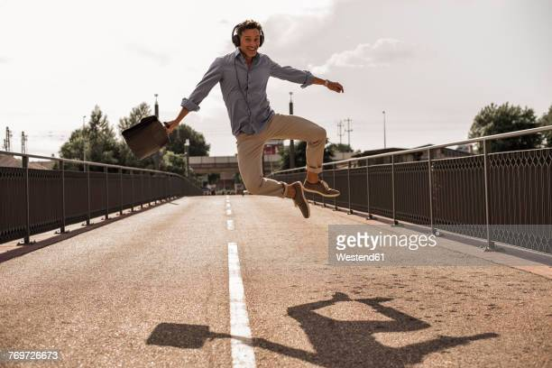 Businessman with headphones and briefcase jumping for joy on a road