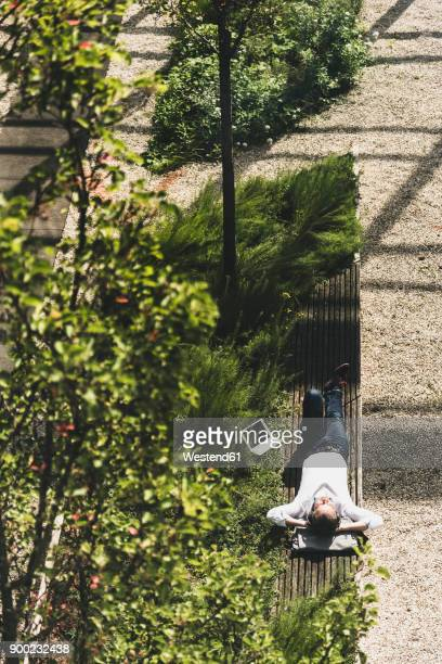 Businessman with headphones lying on a bench next to tablet
