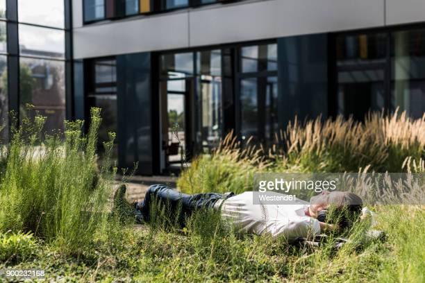 Businessman with headphones lying on a bench outside office building