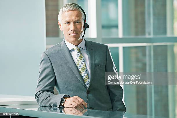 Businessman with headset leaning against desk