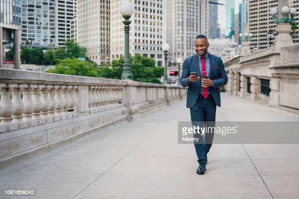 zakenman met headset wandelen in chicago met zijn gsm - goed nieuws stockfoto's en -beelden