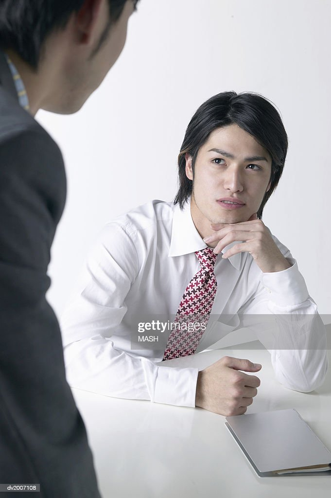 Businessman With His Hand on His Chin Looking at Another Businessman Across a Table : Stock Photo