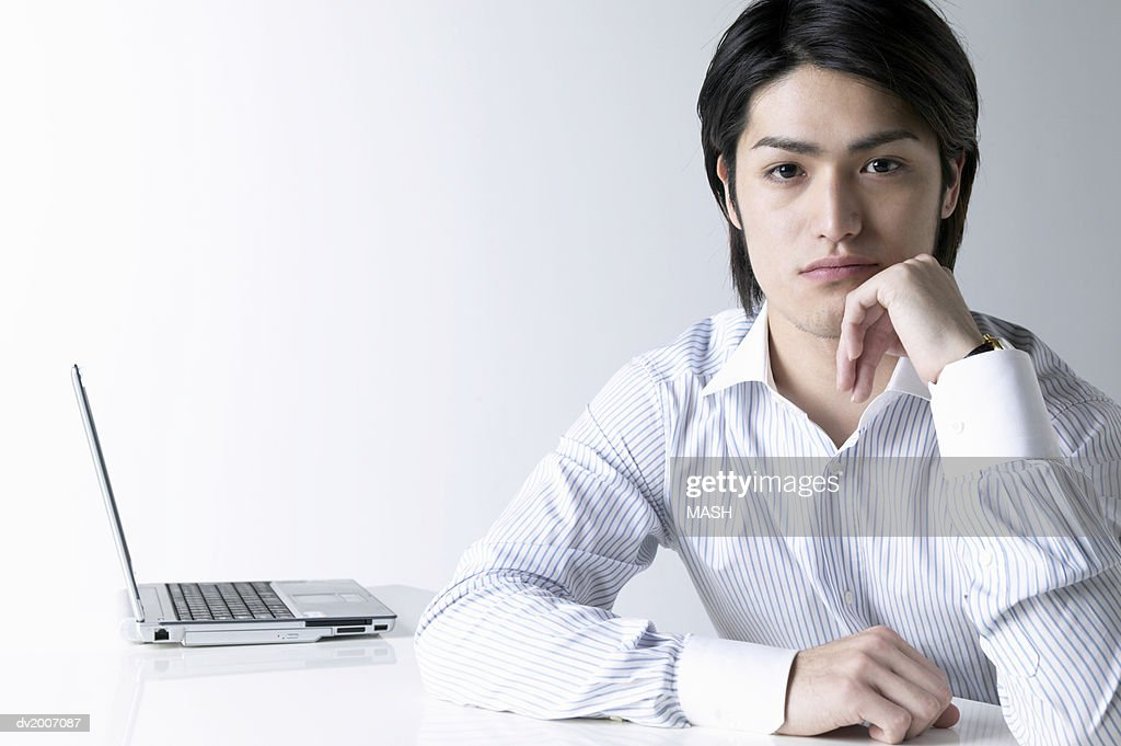 Businessman With His Hand on His Chin Sitting by a Laptop : Stock Photo