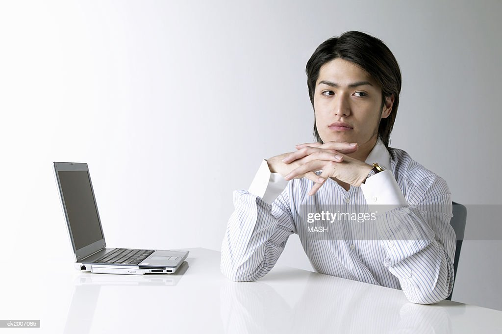 Businessman With His Hands on His Chin Sitting by a Laptop : Stock Photo
