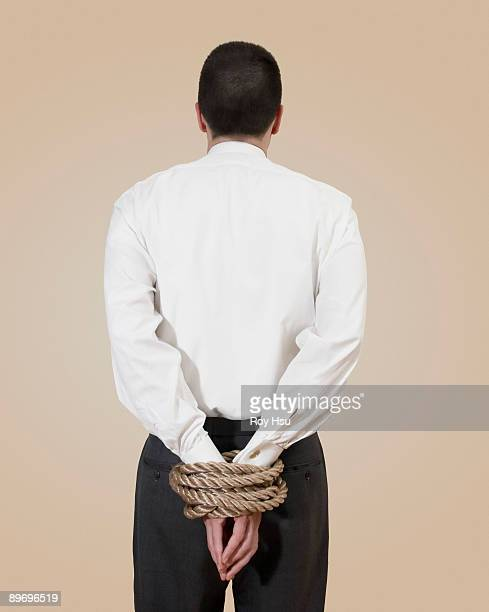 Businessman with his hands tied behind his back