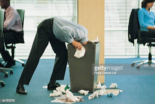 Businessman With His Head Inside an Office Bin