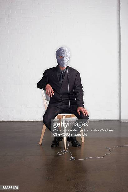 Businessman with his head wrapped in string