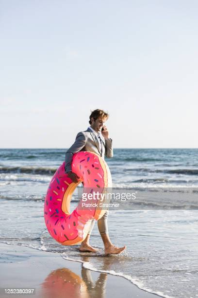 businessman with inflatable donut on sunny ocean beach, los angeles, california - city of los angeles stock pictures, royalty-free photos & images