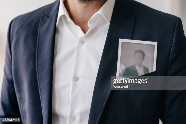 Businessman with instant photo in pocket of his jacket
