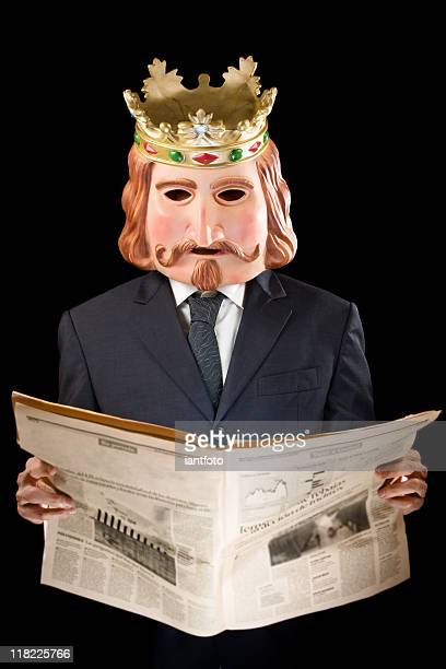 businessman with king mask reading news - symbolism stock pictures, royalty-free photos & images