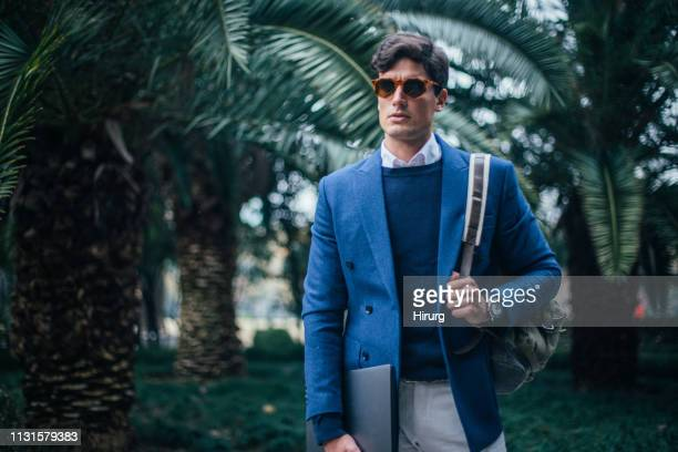businessman with laptop and backpack walking in the park - blue suit stock pictures, royalty-free photos & images