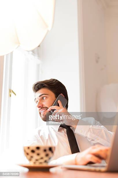Businessman with laptop and cup of coffee on cell phone