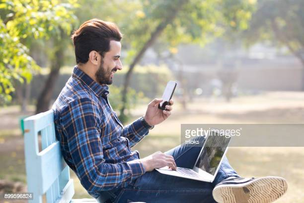 businessman with laptop and mobile phone at park - one man only stock pictures, royalty-free photos & images