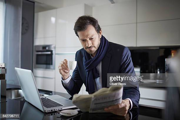 Businessman with laptop and newspaper in kitchen
