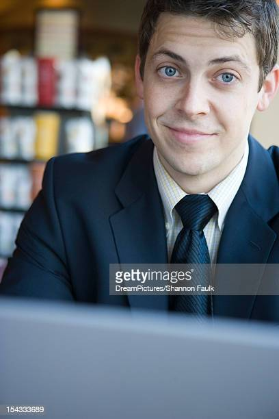 Businessman with laptop at cafe smiling at camera