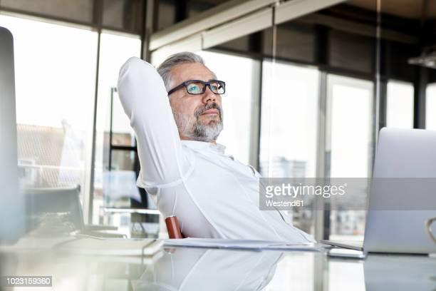 businessman with laptop at desk in office thinking - hände hinter dem kopf stock-fotos und bilder