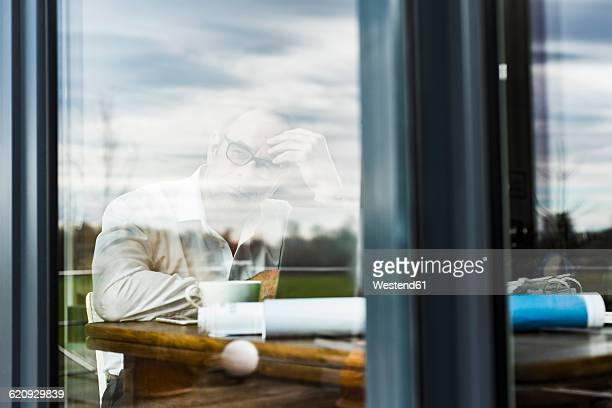 Businessman with laptop at wooden table thinking