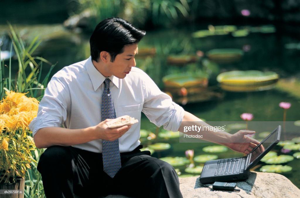 Businessman with laptop eating outside : Stock Photo