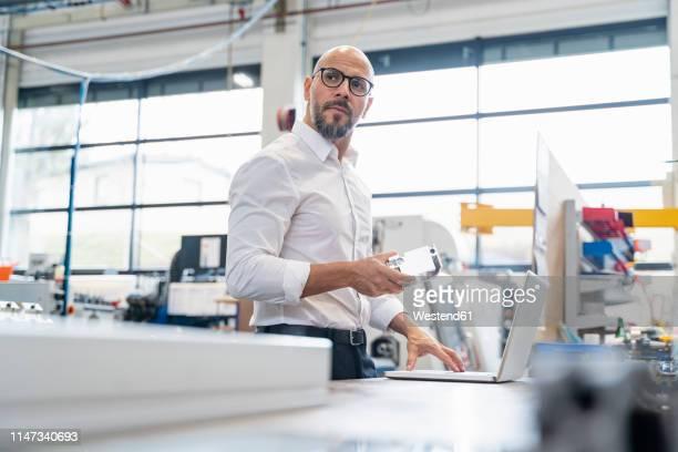 businessman with laptop holding workpiece in factory - ingenieur stock-fotos und bilder