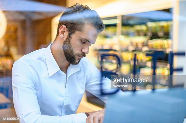 Businessman with laptop in a cafe checking the time