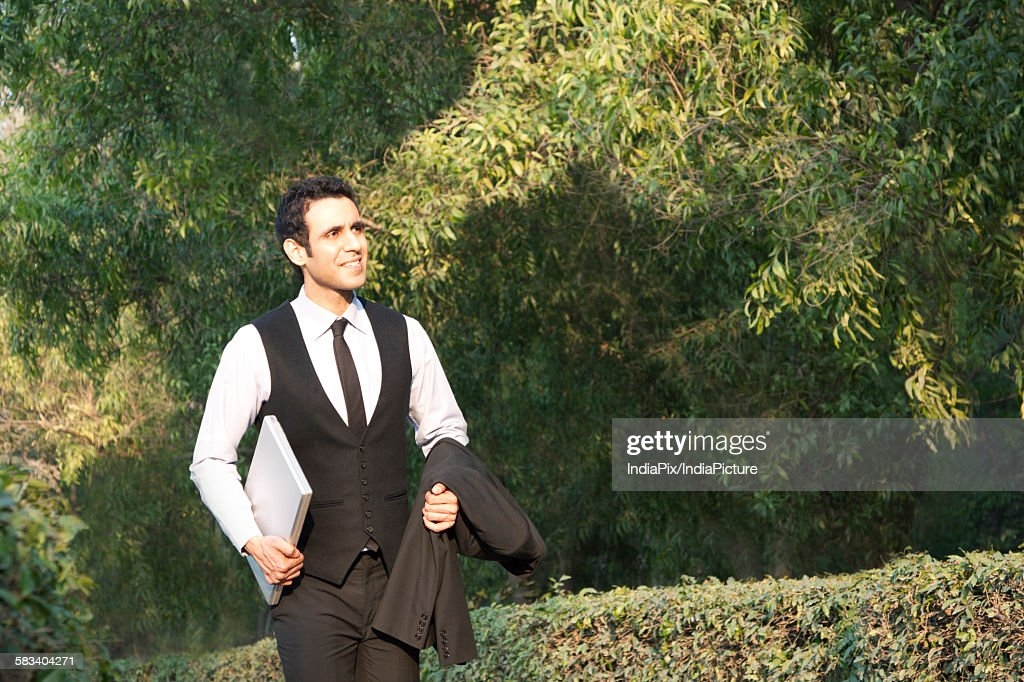 Businessman with laptop in a park , INDIA , DELHI : Stock Photo
