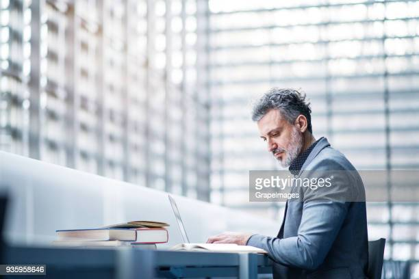 businessman with laptop in an office or a library. - grey suit stock pictures, royalty-free photos & images