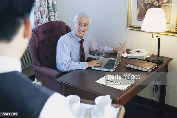 Businessman with laptop in hotel room