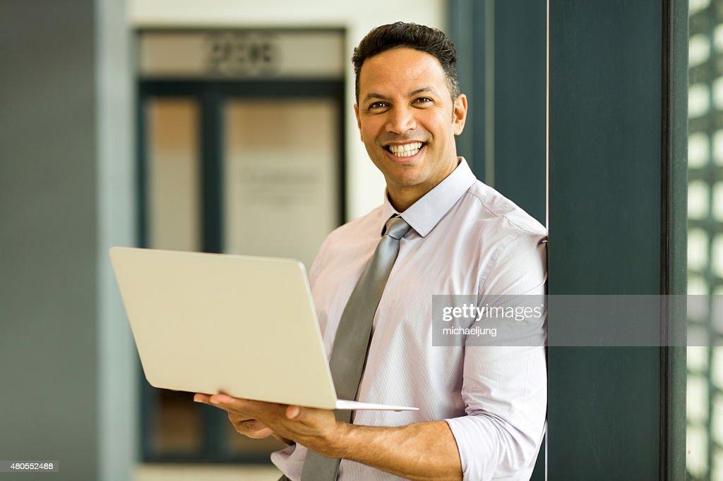 Empresário com o laptop no escritório : Foto de stock
