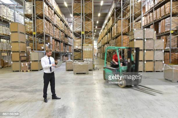 businessman with laptop in warehouse and worker on forklift - finanzen und wirtschaft stock-fotos und bilder