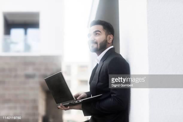 businessman with laptop looking around buildings - sigrid gombert stock-fotos und bilder