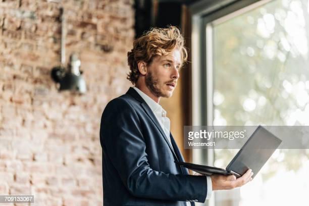 businessman with laptop looking away - oprichter stockfoto's en -beelden