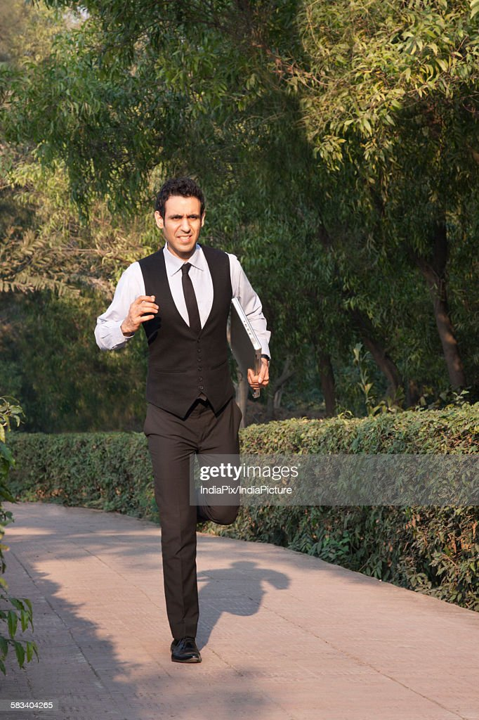 Businessman with laptop running in a park , INDIA , DELHI : Stock Photo